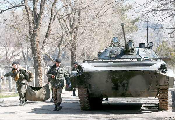 Soldados ucranianos abandonan el territorio de una zona militar en Perevalnoye que ha sido tomada por los rusos a las afueras de Simferópol.