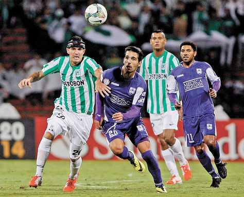 Jugada. Cardacio (violeta), de Defensor Sporting, lucha por el balón con Bernal, de Atlético Nacional. (FOTO: EFE)