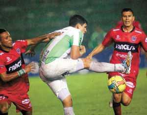 El delantero orientista Richard Estigarribia pifia el balón ante la marca de Ramiro Ballivián, anoche en el Tahuichi. AFKA.
