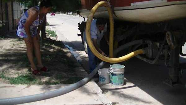 Vecinos se aprovisionan mediante cisternas que reparten agua en los diferentes barrios. (Foto: El Tribuno)