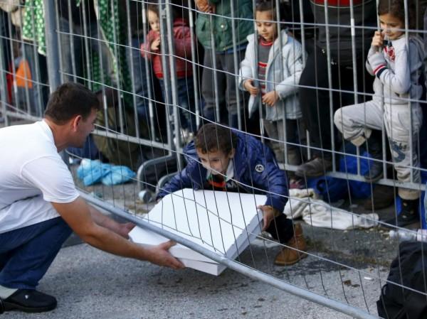 Un socorrista sirve una pizza a un grupo de niños. (Foto: Reuters)